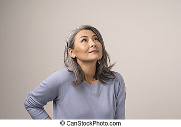 Woman of Mongolian Appearance with Gray Hair on a White Background.