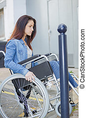 woman of wheelchair having problem moving in the city
