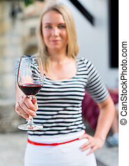 Woman offering glass of red wine outdoors.