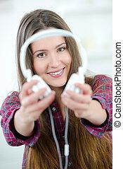 Woman offering you her headphones