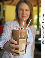 Woman offers a cold chocolate cocktail.