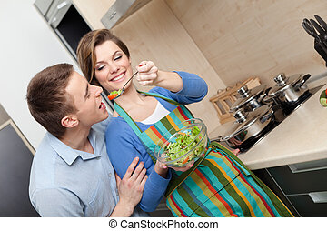 Woman offers her husband to taste salad with vegetable
