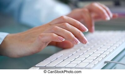 Woman office worker typing on the keyboard and works with...