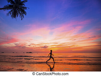 Woman oiled silhouette running on tropical beach during amazing sunset.