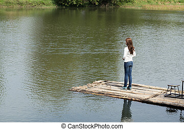 Woman on a bamboo raft in river