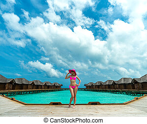 Woman on a beach jetty at Maldives