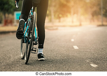 Woman on a bicycle on a road in the park.
