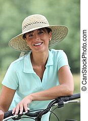 Woman on a bicycle wearing a hat