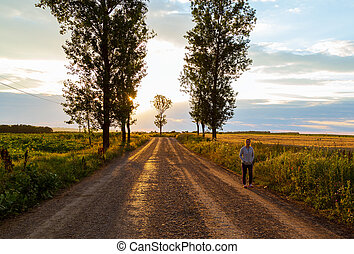 Woman on a country road with the sun among the trees