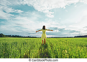 Woman on a green field - Young woman with her arms wide...