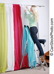 Woman on a ladder housework - woman hanging up curtains