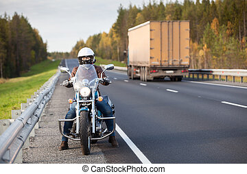 Woman on a motorcycle stands on the roadside of a country highway near passing freight truck