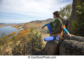 woman on a rock in the mountains