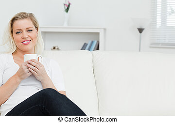 Woman on a sofa drinking a coffee