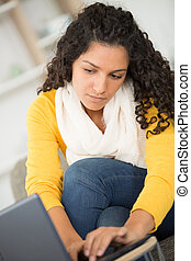 woman on a sofa with laptop