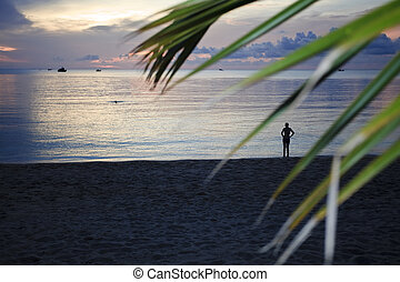 Woman on a tropical beach at sunset.