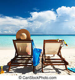 Woman on a tropical beach in chaise lounge at Maldives