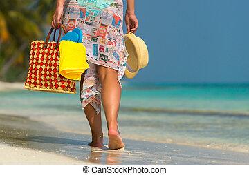 Woman on a tropical beach with orange bag
