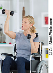 woman on a wheelchair doing physiotherapy at home