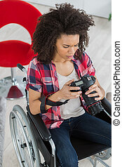 woman on a wheelchair looking image in the camera