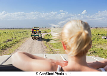 Woman on african wildlife safari observing nature from open roof safari jeep.