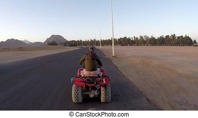Woman on an ATV in the Egyptian desert. GoPro shot.