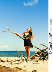 Woman on beach branches.