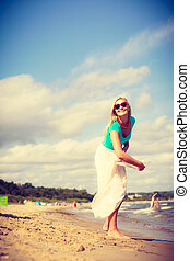 Woman on beach throwing sun hat