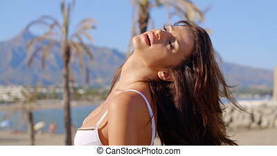 Woman on Beach Tossing Hair Back with Eyes Closed