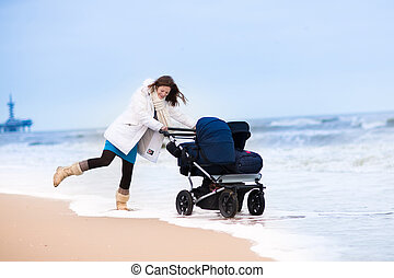Woman on beach with double stroller - Happy active young...
