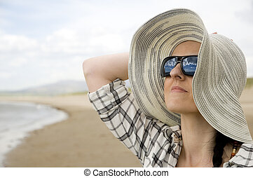 woman on beach with sun hat