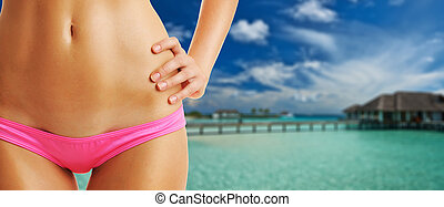 Woman on beautiful beach with water bungalows
