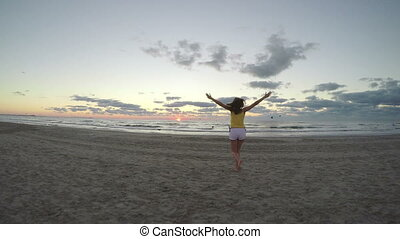 Woman on beautiful sandy beach running towards the sea