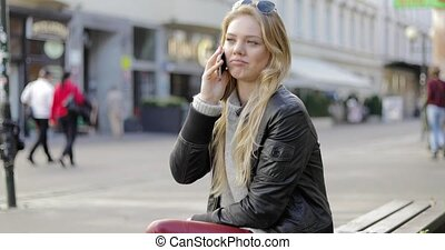 Woman on bench and speaking on phone - Beautiful young woman...