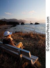 woman on bench overlooking beach