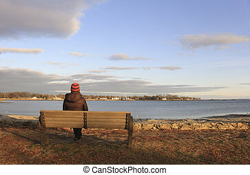 woman on bench overlooking ocean