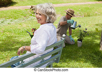 Woman on bench while man watering plant at park - Happy...