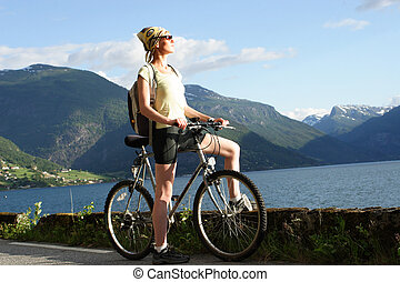 Sporty woman with her bike looking at the mountain
