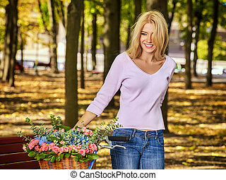 Woman on bicycle with flowers basket autumn park outdoor.