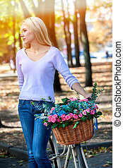 Woman on bicycle with flowers basket summer park outdoor.