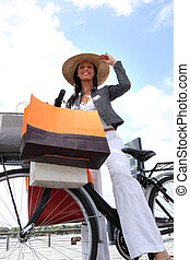 Woman on bike holding shopping bags