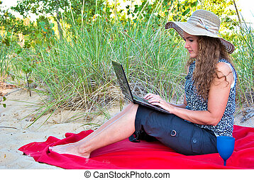 woman on blanket with laptop