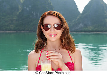 Woman on boat enjoying with glass of juice among the islands