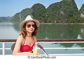 Woman on boat with glass of juice among the islands