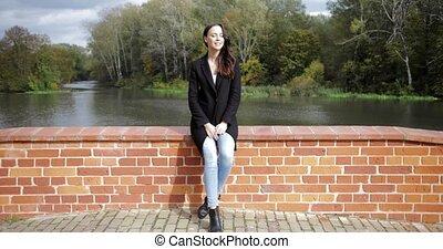 Woman on bridge enjoying weather - Beautiful woman in black...