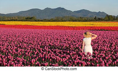Woman on colourful tulip fields.