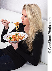 woman on couch eating spaghetti