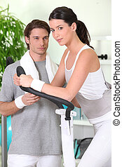 Woman on cross trainer with sports coach