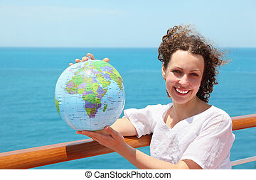 woman on deck of ship among sea with ball in form of globe