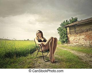 Woman on deckchair at countyside